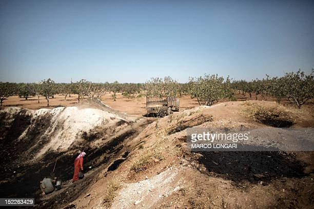 Syrian women work with the waste of pressed olives mixed with water and left to dry in the sun in a field near the battled Syrian city of alBab on...