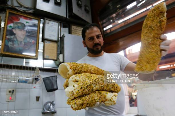 A Syrian worker makes traditional icecream at the famous 'Bagdash' sweet shop in the Hamidiyeh popular market in the old part of the capital Damascus...