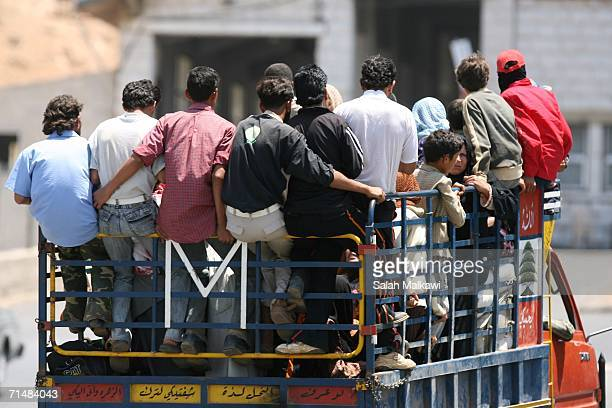 Syrian workers head to cross the LebaneseSyrian border on July 19 2006 at Masnaa Lebanon Two Israeli soldiers and one Hezbollah militant were killed...