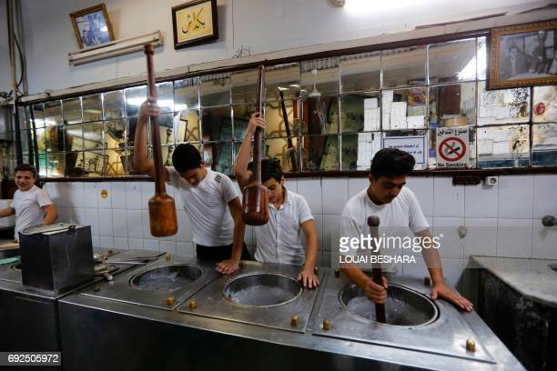 Syrian workers make traditional icecream at the famous 'Bagdash' sweet shop in the Hamidiyeh popular market in the old part of the capital Damascus...