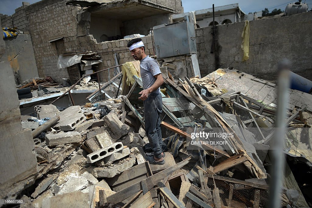 A Syrian wounded man looks at the rubbles of his destroyed house following an airstrike by the Syrian airforce in the northern Syrian city of Aleppo on April 15, 2013. The conflict in Syria, which is now in its third year, has cost 70,000 lives, according to the United Nations.