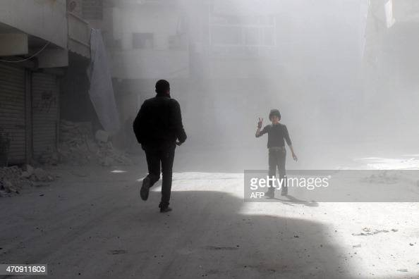 A Syrian young boy flashes the sign of victory amid dust as a man runs in a street of the northern city of Aleppo following a reported Syrian...