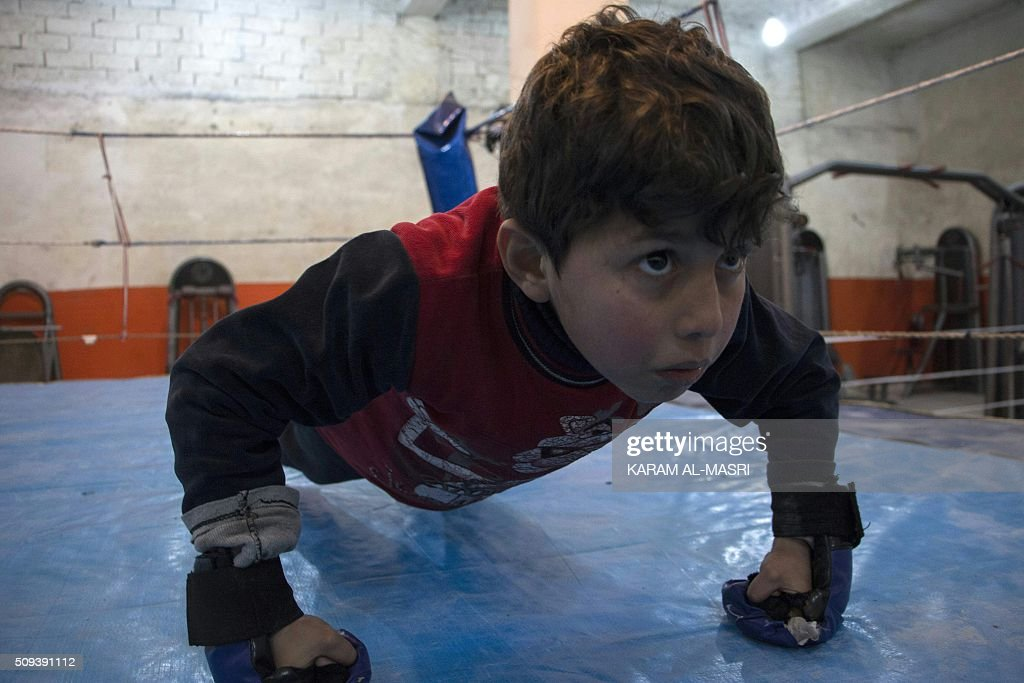 A Syrian young boy takes part in a training session led by a Syrian former national boxing champion at the Shahba boxing club that he founded in Syria's war-torn Aleppo city on February 10, 2016 in a rebel held district of the city. Former champion Shaaban Kattan and his colleague Ahmad Mashallah opened the club in the summer of 2015 to bring boxing back to a conflict-ravaged city. Bathed in the fluorescent light of a sparse basement in Aleppo, young boys pummel red punching bags under the close supervision of a former national boxing champion MASRI