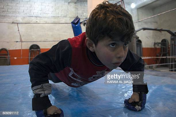 A Syrian young boy takes part in a training session led by a Syrian former national boxing champion at the Shahba boxing club that he founded in...