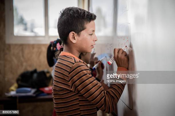 Syrian young boy writes on the white board at school in Al Marj refugee settlement as he learns arithmetic The children here have lost out on a lot...