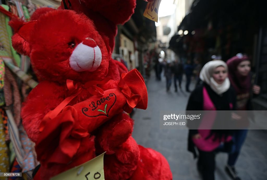 Syrian young women walk past a shop displaying red teddy bears for Valentine's day in Damascus on February 10, 2016. / AFP / JOSEPH EID