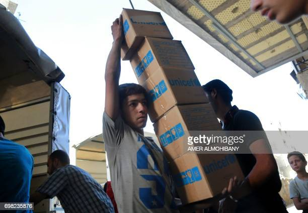 A Syrian youth carries boxes of aid donated by UNICEF in the rebel held and besieged town of Harasta in the Eastern Ghouta region outside Damascus on...