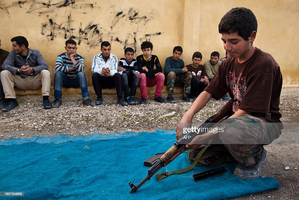 Syrian youth holds an AK-47 assault rifles as he takes part in a military training on January 23, 2013 at a former school turned into a 'military academy' in Tlaleen in the northern Syria's Aleppo province. Bored at home and eager to join their older brothers and fathers on the frontline against President Bashar al-Assad's army, Syrian teenagers are joining the rebel cause, oblivious to international laws prohibiting child combattants.
