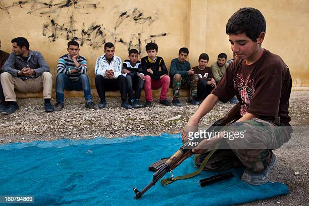 Syrian youth holds an AK47 assault rifles as he takes part in a military training on January 23 2013 at a former school turned into a 'military...