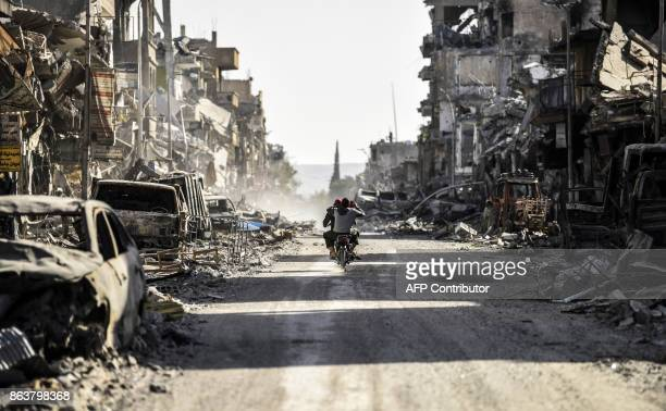 Syrian youth uses his cell phone to film the destroyed vehicles and heavily damaged buildings down a street in Raqa on October 20 after a Kurdishled...