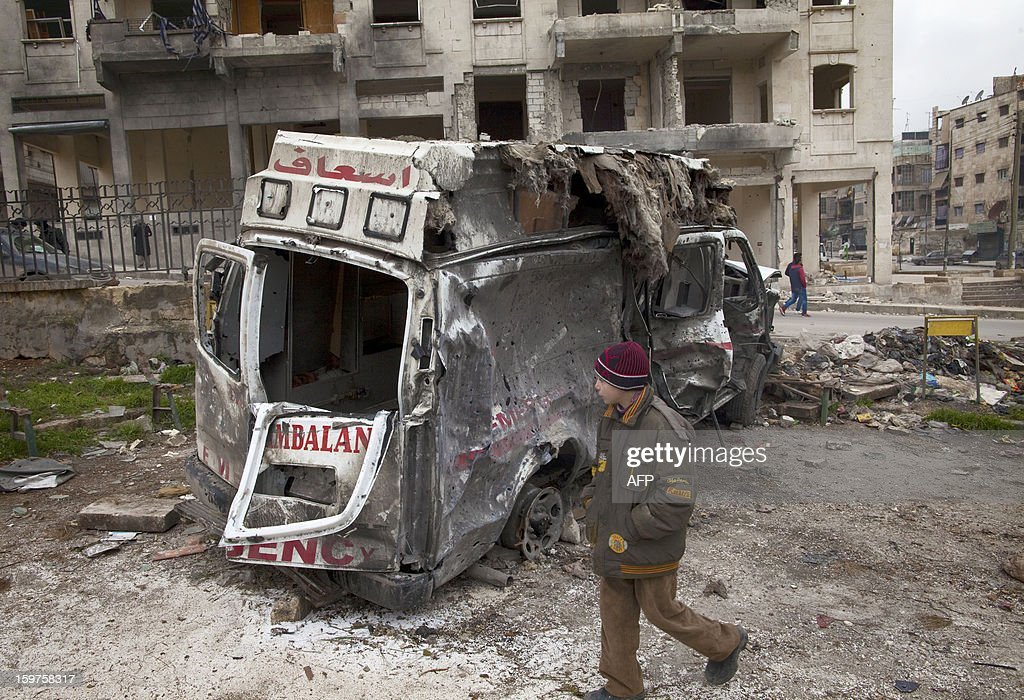 Syrian youth walks past a destroyed ambulance in the Saif al-Dawla district of the war-torn northern city of Aleppo on January 12, 2013. An accident and emergency centre in Aleppo uses an abandoned supermarket to conceal a fleet of 16 ambulances, just 10 of which are in working order and are driven by 22 staff members. AFP PHOTO/JM LOPEZ