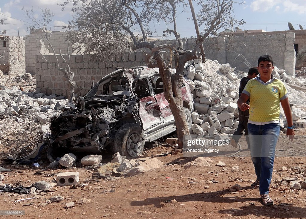 Syrian youth walks past the wreckage of a vehicle following the USled coalition's airstrikes against the Islamic State of Iraq and the Levant on a...
