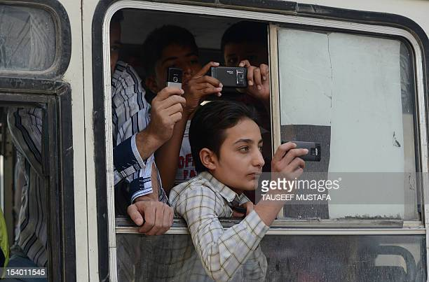 Syrian youths inside a vehicle film a protest against the regime of Syrian President Bashar alAssad with their phones in the northern city of Aleppo...