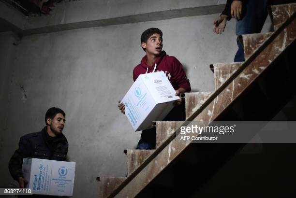Syrian youths unload humanitarian aid parcels from a Syrian Red Crescent truck in the besieged rebelheld Eastern Ghouta region outside Damascus on...