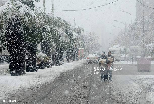 Syrian youths walk back with sacs of pitta bread from a bakery in Damascus under heavy snow fall on January 7 2015 A fierce winter storm lashing the...