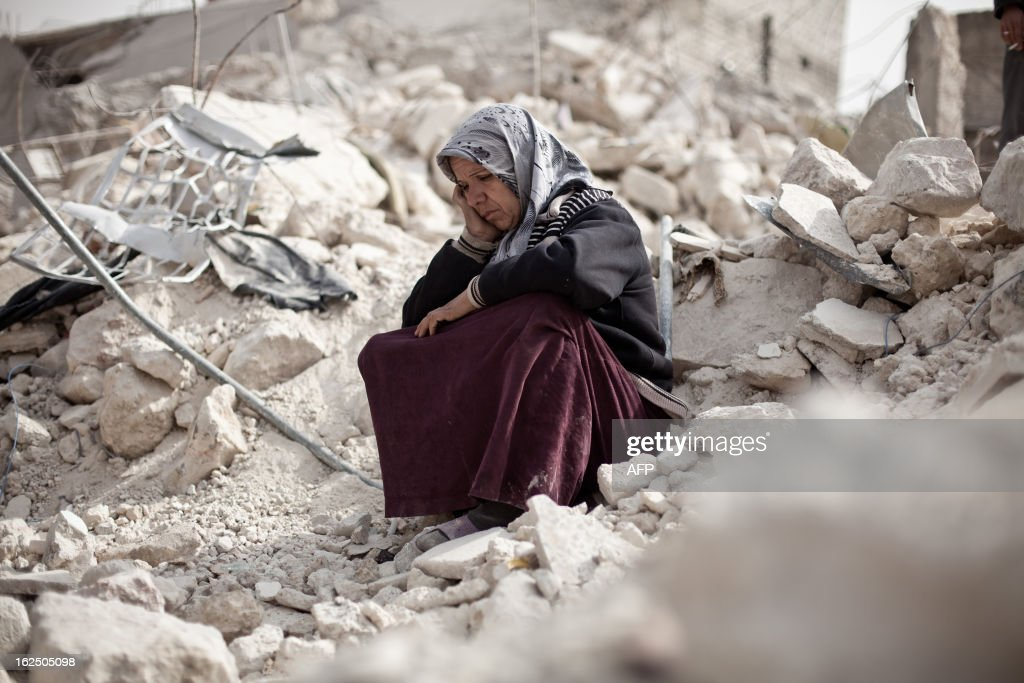 Syrian Zakia Abdullah sits on the rubble of her house in the Tariq al-Bab district of the northern city of Aleppo on February 23, 2013. Three surface-to-surface missiles fired by Syrian regime forces in Aleppo's Tariq al-Bab district have left 58 people dead, among them 36 children, the Syrian Observatory for Human Rights said on February 24. AFP PHOTO/PABLO TOSCO