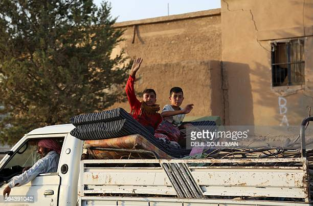 SyrianKurdish boys wave on the back of a truck as they return to the northeastern Syrian city of Hasakeh on August 23 after regime forces and Kurdish...