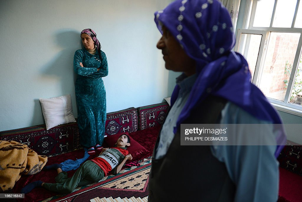 Syrian-Kurdish family and their handicapped son gather in the living-room of a house in the Turkish town of Ceylanpinar, bordering Syria, on November 10, 2012. Thousands of Kurds have fled Syrian army attacks on the strategic border town of Ras al-Ain, running for their lives to Turkey as homes were shelled and dead fighters lay bleeding in the streets.