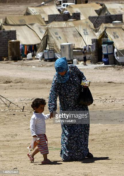SyrianKurdish woman and child walk on June 8 2012 in the Domiz refugee camp 20 km southeast of Dohuk city which hosts refugees of all stripes from...