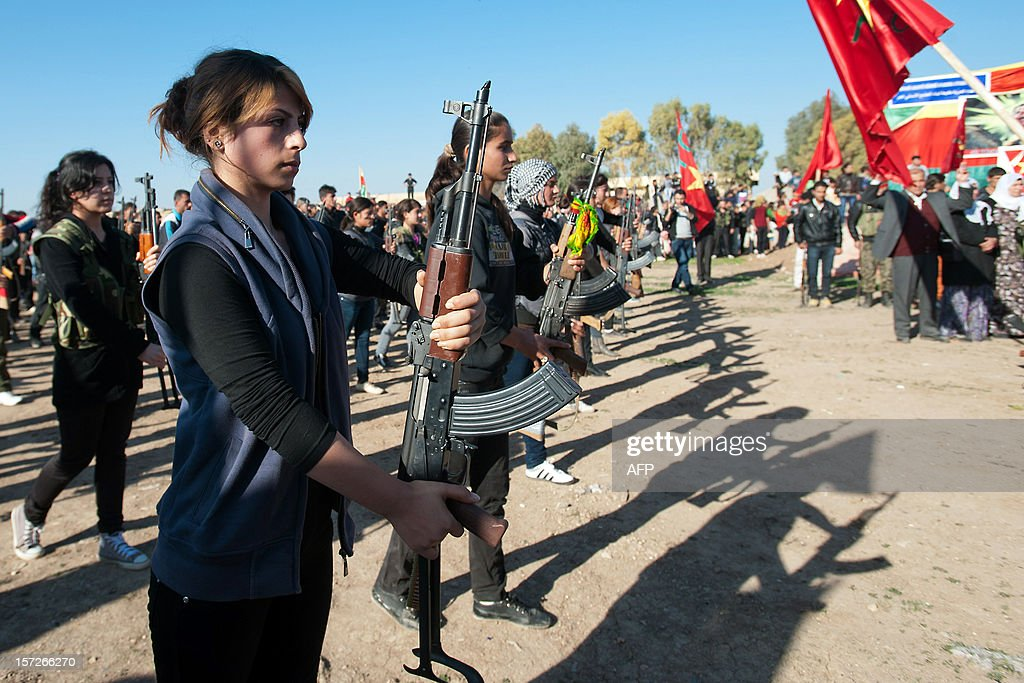 Syrian-Kurdish women and members of the Popular Protection Units (YPG), an armed opposition group fighting against the Syrian government, stand guard during the funeral of a comrade, Basil Zeydan, in the northern Syrian border village of al Qamishli on December 1, 2012. The Syrian army shelled the outskirts of Damascus in a drive to establish a secure perimeter around the capital, including the key airport road that has come under sustained rebel attack.