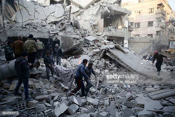 Syrians and civil defence workers evacuate victims from the rubble of a destroyed building following air strikes on the Eastern Ghouta town of Douma...