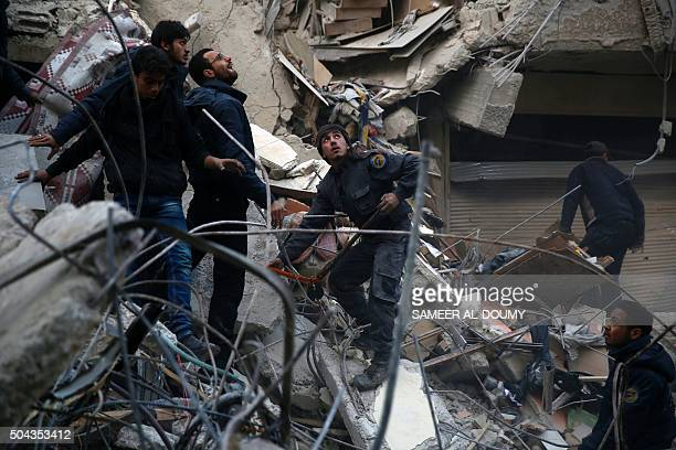 TOPSHOT Syrians and civil defence workers search for victims amid the rubble of a destroyed building following air strikes on the Eastern Ghouta town...