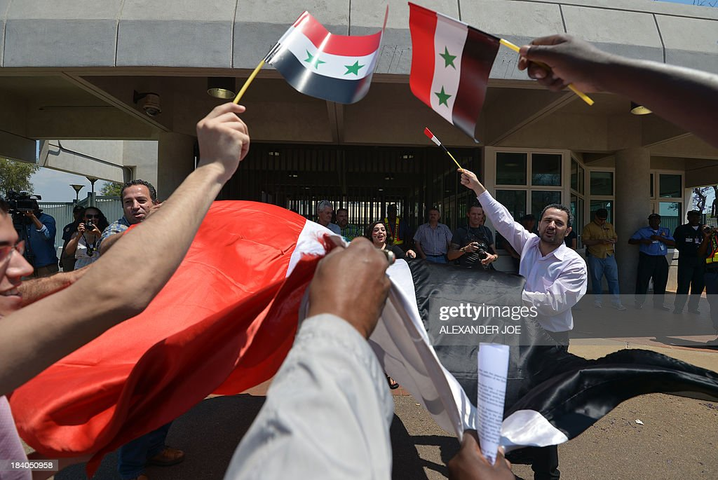 Syrians and members of the Congress of South African Trade Unions (COSATU) wave Syrian flags outside the US embassy in Pretoria on October 11, 2013 during a protest against US intervention in Syria and the conflict in the war-torn country which they consider to be 'in the interest of imperialism'.