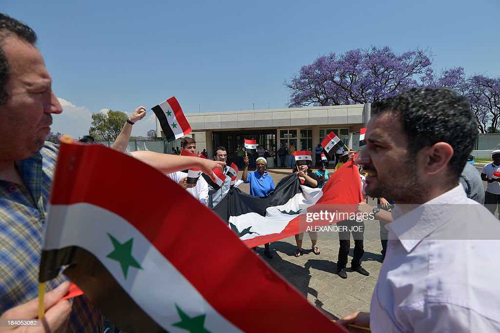 Syrians and members of the Congress of South African Trade Unions (COSATU) wave Syrian flags outside the US embassy in Pretoria on October 11, 2013 during a protest against US intervention in Syria and the conflict in the war-torn country which they consider to be 'in the interest of imperialism'. AFP PHOTO / ALEXANDER JOE