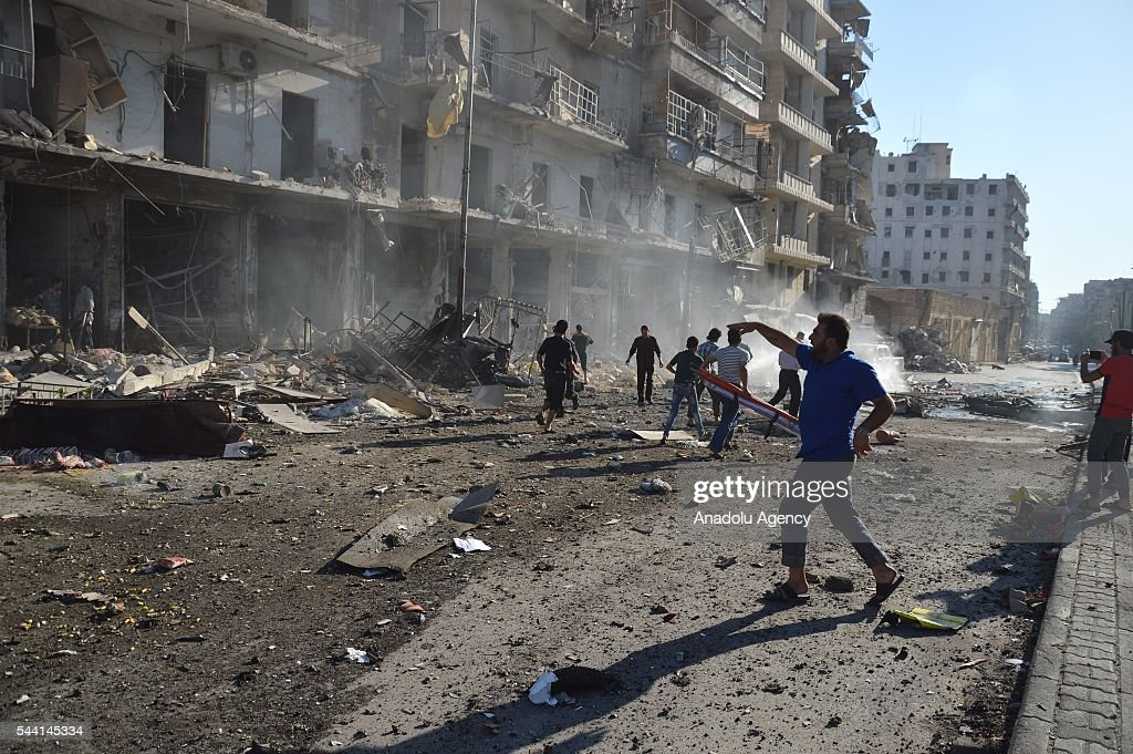 Syrians are seen aroun the wreckage of the buildings after belonging to the Syrian army carried out airstrikes on residential areas in the opposition controlled Tariq al-Bab neighborhood in Aleppo, Syria on July 1, 2016.