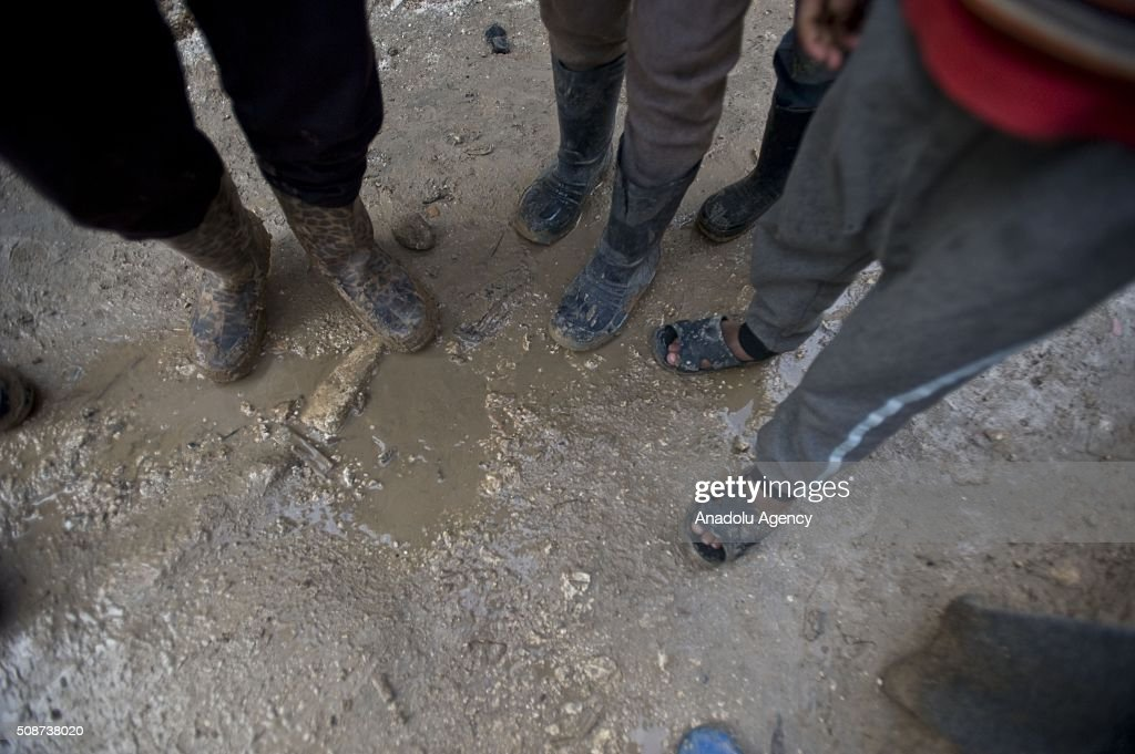 Syrians are seen at mud covered road at tent city built by IHH Humanitarian Relief Foundation near the Bab al-Salam border gate on Turkey's border in Azez district of Aleppo as they flee to Turkey to escape heavy Syrian regime and Russian airstrikes, on February 6, 2016.