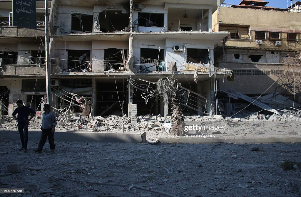 Syrians are seen in front of the damaged buildings after Assad regime war crafts carried out an airstrike over Eastern Ghouta region in Damascus, Syria on February 12, 2016.