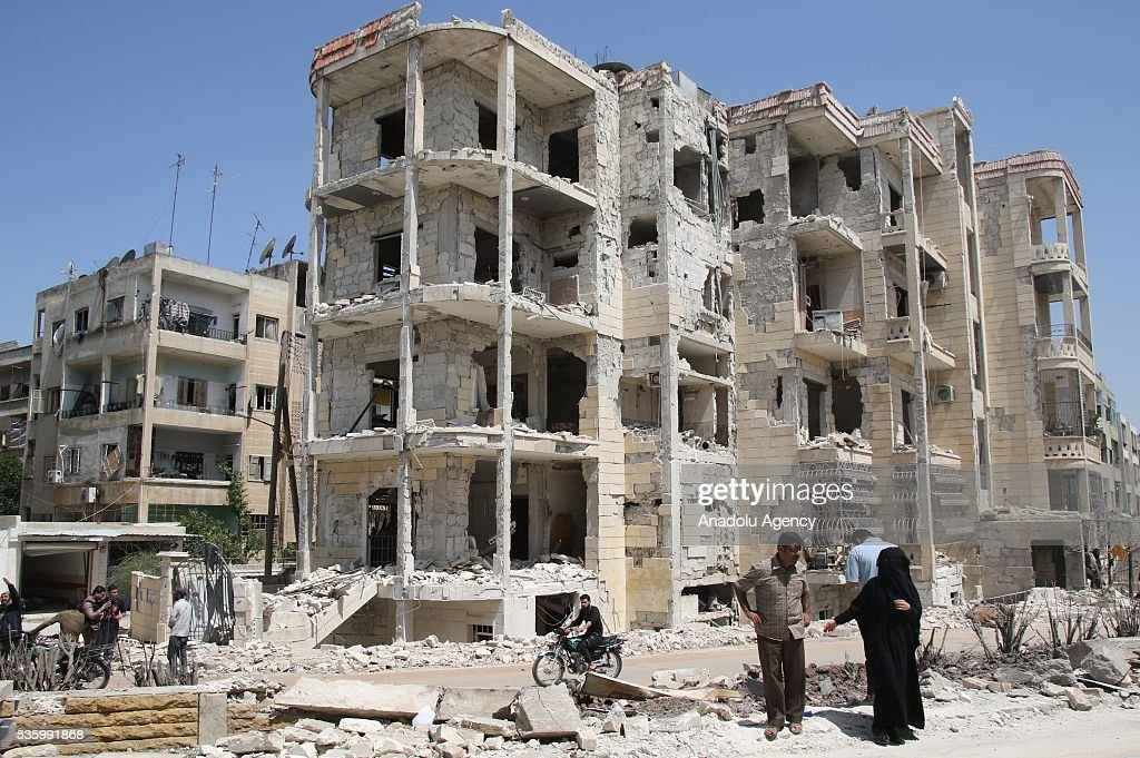 Syrians are seen in front of the debris of a building after the Russian airstrikes targeted Sevra district of Idlib in Syria on May 31, 2016.