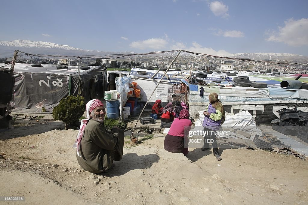 """Syrians are seen outside their makeshift houses at a refugee camp in the village of Saadnayel in the Lebanese Bekaa valley on March 6, 2013. The number of Syrians who have fled their war-ravaged country and are seeking assistance has now topped the 1 million mark, the UN refugee agency said, warning that Syria is heading towards a """"full-scale disaster."""" AFP PHOTO/JOSEPH EID"""