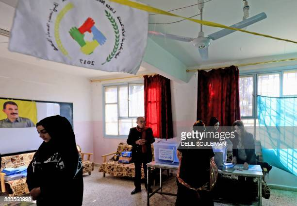Syrians arrive to cast their votes in local elections held in the northeastern Syrian city of Qamishli on December 1 with a flag depicting the image...