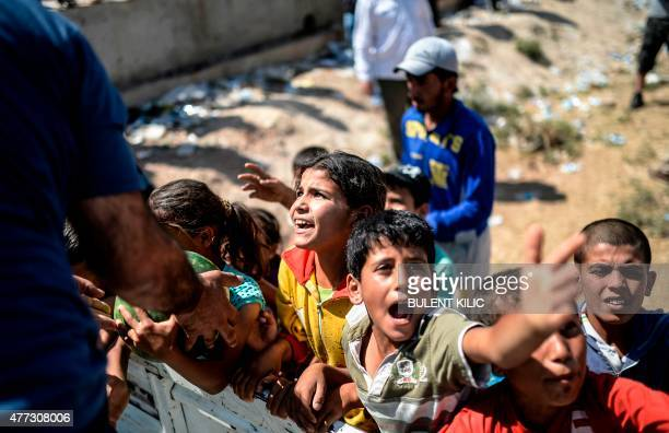 Syrians attend a distribution of watermelons near the Akcakale crossing gate between Turkey and Syria at Akcakale in Sanliurfa province on June 16...