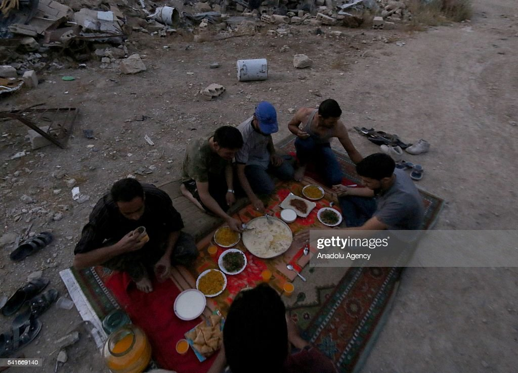 Syrians break their fasts at Iftar time between collapsed buildings during the Islamic holy month of Ramadan at Cobar district of eastern Goutha...