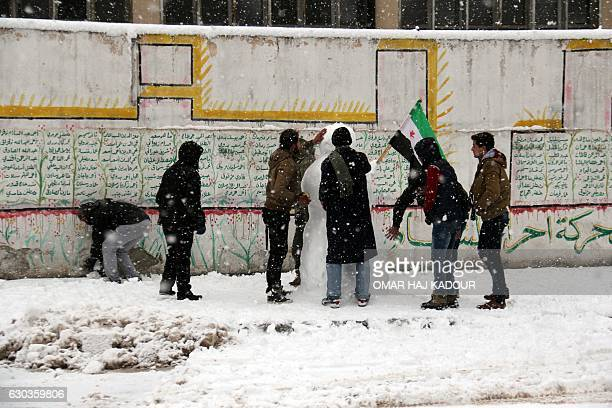 TOPSHOT Syrians build a snowman during a storm that brought snow heavy rain and high winds in the Syrian town of Binnish on the outskirts of Idlib on...