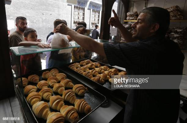 Syrians buy croissants in the old city of Damascus on May 25 ahead of the start of the Muslim holy fasting month of Ramadan / AFP PHOTO / Louai...