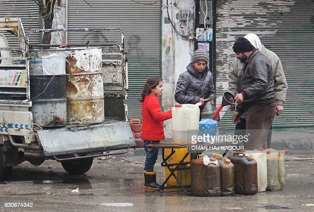 Syrians buy petrol on a street in the northwestern city of Idlib on December 30 2016 A fragile calm is holding across Syria after a truce brokered by...