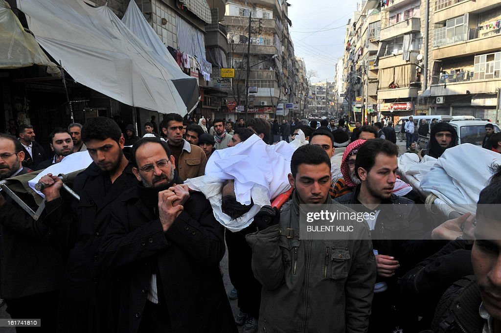 Syrians carry a body of a fighter during a funeral after Friday prayer in the northeastern city of Aleppo on February 15, 2013. Turkish artillery struck back after a shell fired from neighbouring Syria ploughed into Turkish territory without causing any casualties, the state-run news agency reported. AFP PHOTO/BULENT KILIC