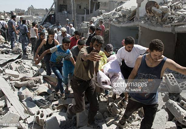 Syrians carry a body on a stretcher over the rubble after a missile fired by Syrian government forces hit a residential area in the Maghayir district...