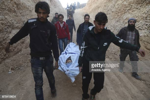 Syrians carry a dead body after Assad regime's war crafts carry out intensifying airstrikes over residential areas of Douma town of the Eastern...
