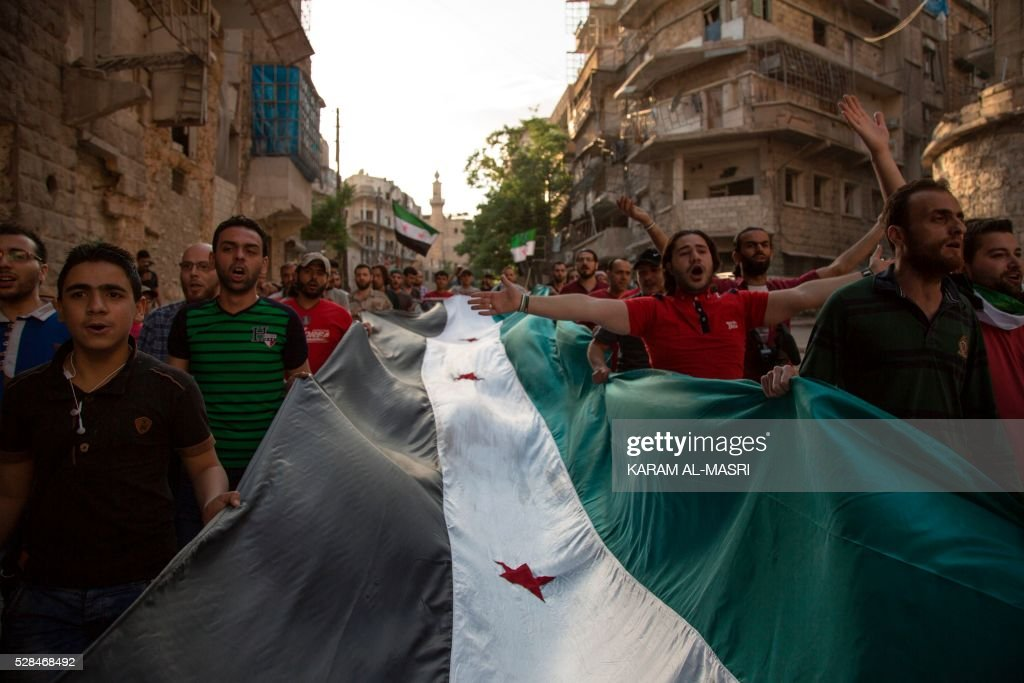 Syrians carry a giant pre-Baath Syrian flag as they shout slogans during an anti-regime protest in the rebel-held Bustan al-Qasr district in eastern Aleppo on May 5, 2016. The Syrian army said late on May 4 that it had agreed to calls from Russia and the United States for a two-day truce in Aleppo that would begin from 1:00 am on May 5. Renewed fighting in recent days, especially in and around Aleppo, had threatened the full collapse of the February 27 ceasefire agreement, a landmark in attempts to finally resolve a conflict that has left more than 270,000 dead. / AFP / KARAM