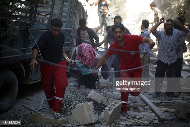 Syrians carry a victim at the site of Assad regime forces' air attack targeting a market in the opposition controlled Damascus suburb of Douma Syria...