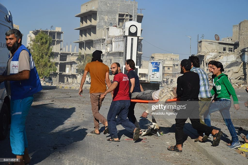 Syrians carry a wounded after belonging to the Syrian army carried out airstrikes on residential areas in the opposition controlled Tariq al-Bab neighborhood in Aleppo, Syria on July 1, 2016.