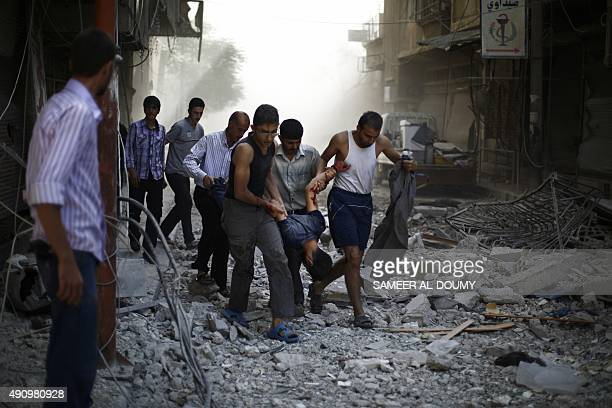 Syrians carry a wounded man following reported air strikes by Syrian government forces on the rebelheld town of Douma east of the Syrian capital...