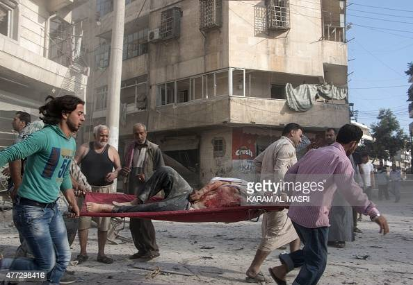 Syrians carry a wounded man on a stretcher following a reported barrel bomb attack by government forces on a the rebelheld area of Maadi in the...
