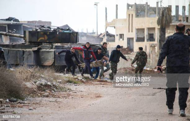 TOPSHOT Syrians carry an injured youth on a stretcher pickup truck in the rebelheld area of Daraa in southern Syria on February 4 2017 / AFP /...