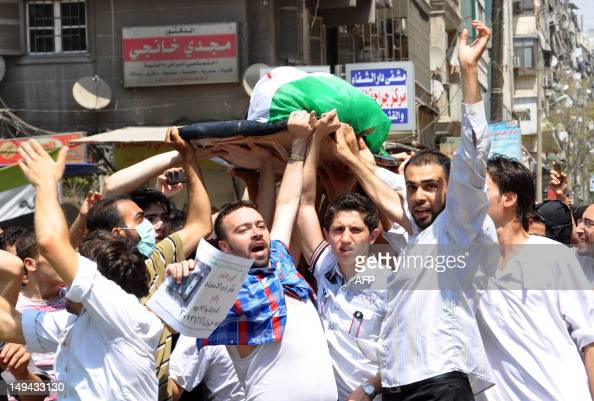 Syrians carry the body of a man allegedly killed in the bombardment of Sukari southwest of the restive city of Aleppo by regime forces on July 27...