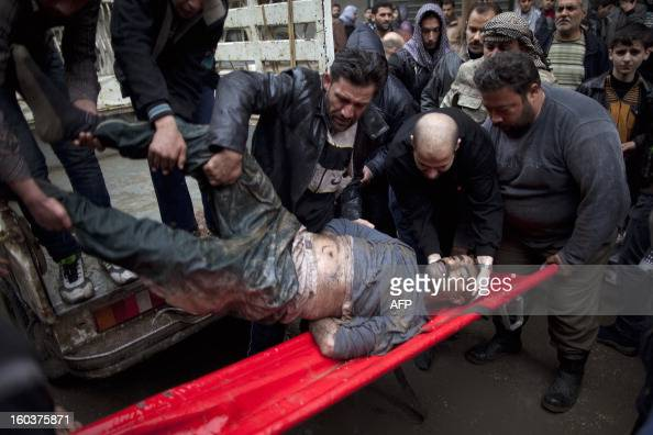 Syrians carry the body of a man who was found in the Quweiq river outside the Yarmuk school in the Bustan alQasr district of the northern city of...